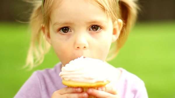 Close up of a little girl eating a cupcake and smiling Royalty-free stock video