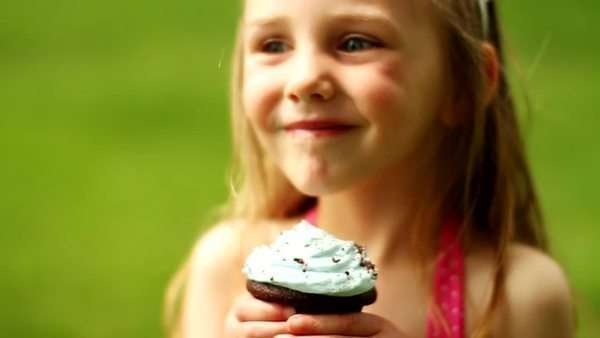 Little girl holding cupcake and smiling Royalty-free stock video