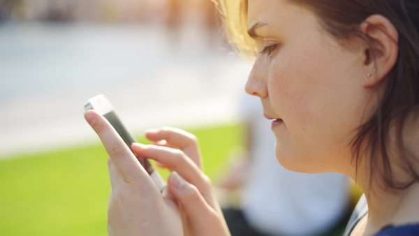Close-up shot of beautiful young Woman using mobile phone in city park Royalty-free stock video