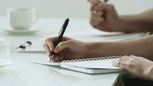 Close-up of a woman's hand taking notes during a meeting Royalty-free stock video
