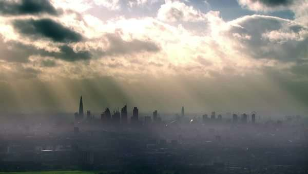 Dramatic aerial view of the London skyline on a hazy autumn morning with rays of light beaming through the clouds above. Royalty-free stock video