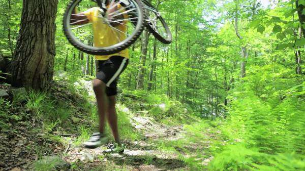 Male cyclist carrying bike through forest Royalty-free stock video