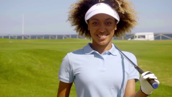 Single cheerful female golfer in blue short sleeve shirt walking with golf club on green turf grass course Royalty-free stock video