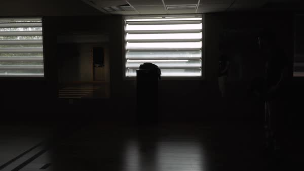 Medium shot of a man standing in a dark and empty room Royalty-free stock video