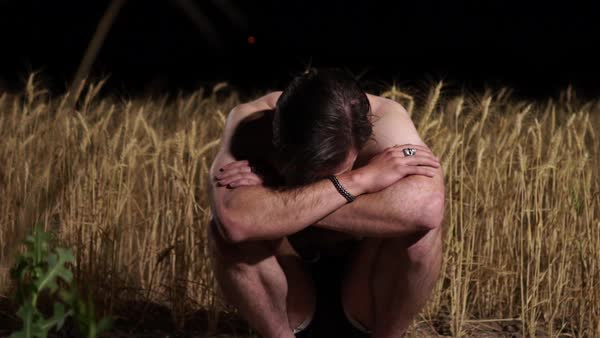 Medium shot of a man squatting in a grain field at night Royalty-free stock video