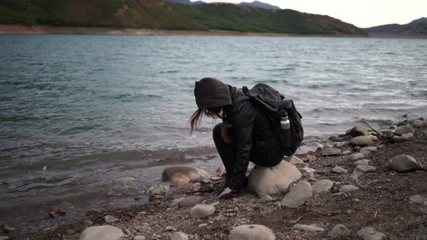 Wide shot of young woman collecting stones on the river bank Royalty-free stock video