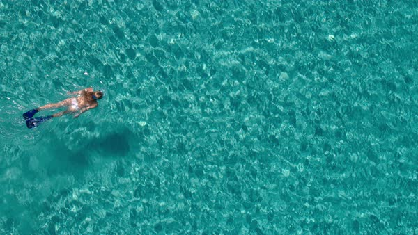 Aerial - Top view of young woman snorkeling underwater in crystal clear waters Royalty-free stock video