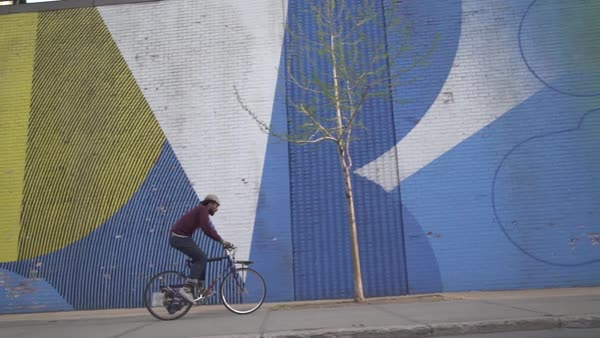 Side view of man riding bicycle on sidewalk against graffiti wall Royalty-free stock video