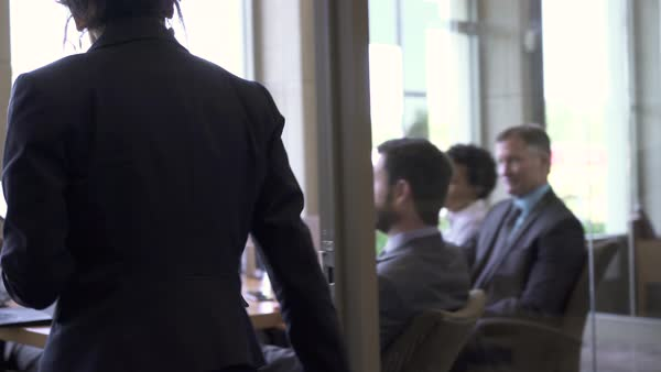 Businesswoman greeting colleagues in board room Royalty-free stock video