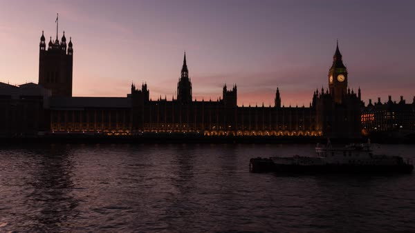 Boats move past Parliament as the sunset light fades from the sky. Royalty-free stock video