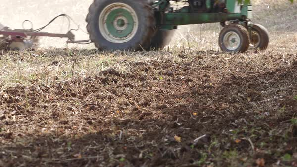 Static shot close-up of a tractor cultivating a field Royalty-free stock video