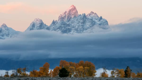 Time lapse of low clouds at sunrise in the Tetons during Fall. Royalty-free stock video