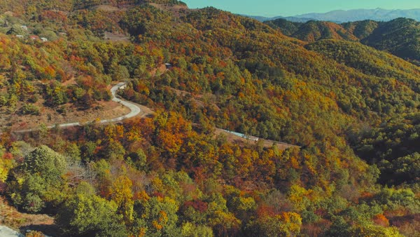 Flyover green lush hills and mountain crossing paved roads stock footage