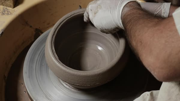 Pot maker creates and shapes pottery on the wheel using his hands Royalty-free stock video