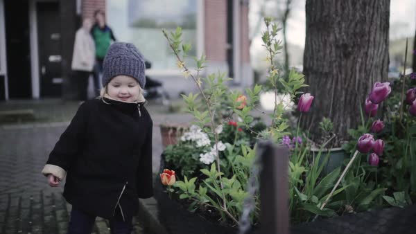 Medium shot of a little girl smelling a flower Royalty-free stock video