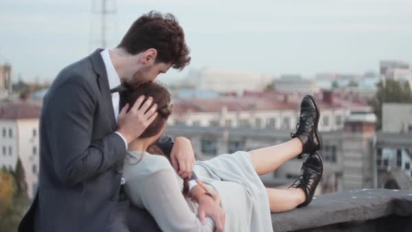 Medium shot of a newlywed couple sitting on a rooftop Royalty-free stock video