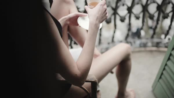 Close-up tracking shot of woman drinking tea on balcony Royalty-free stock video