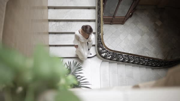 Wide tracking shot of woman walking down on stairs Royalty-free stock video