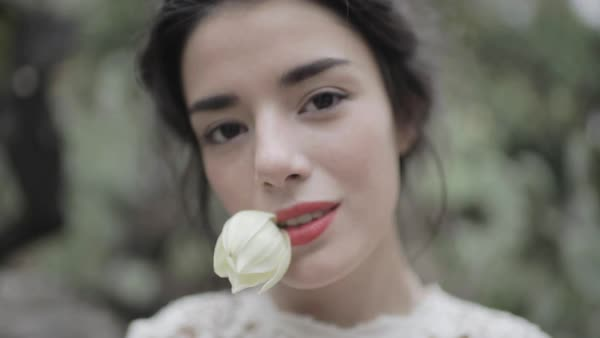 Close-up shot of a woman holding a white flower in her mouth Royalty-free stock video