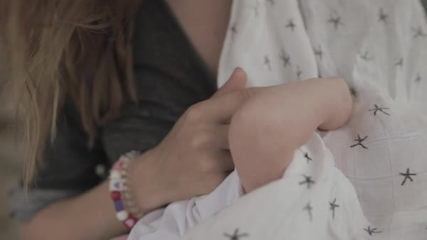 Hand-held shot of a breastfeeding baby holding finger of mother Royalty-free stock video