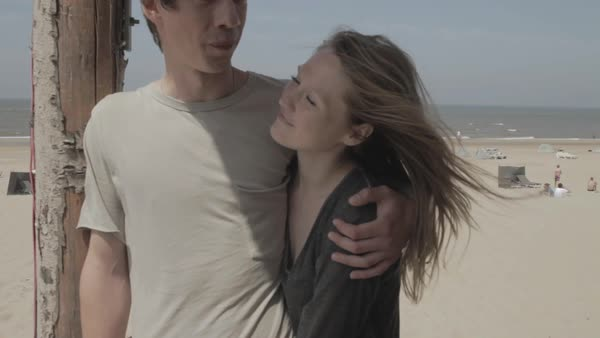 Hand-held shot of a young couple talking on a beach Royalty-free stock video