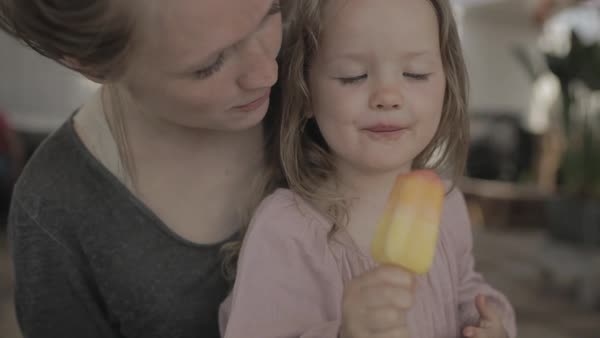 Hand-held shot of a mother and her daughter eating a popsicle together Royalty-free stock video
