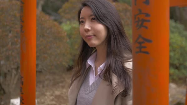 9a959488e9a Slow motion footage of Japanese young woman walking through red Torii gates  at a temple stock footage
