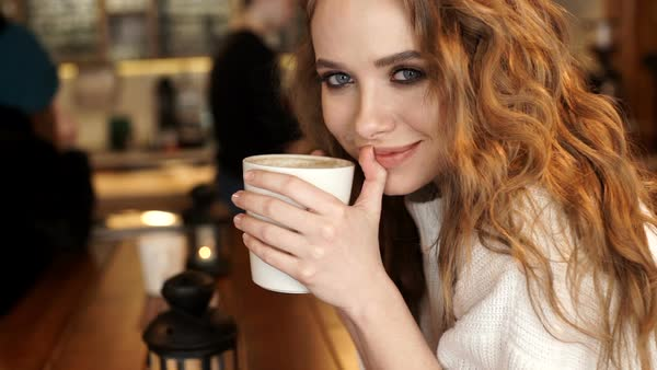 Happy Girl Drinking Coffee And Relaxing In Cafe Smiling