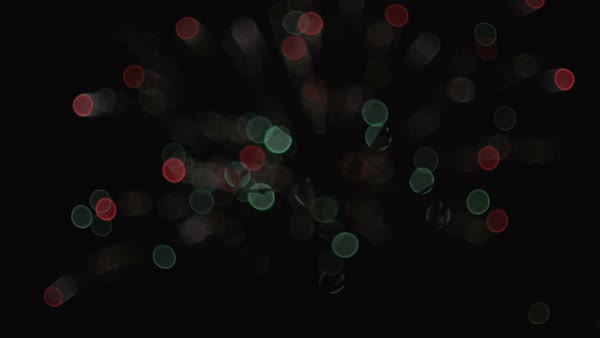 Colorful fireworks bokeh in slow motion at night with tree silhouette in front Royalty-free stock video