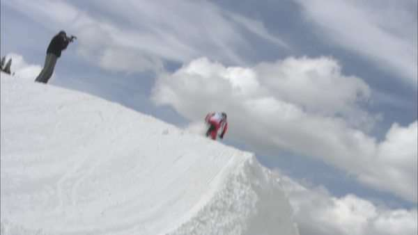 Zooming in shot of a person jumping on a snowmobile Rights-managed stock video