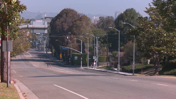 Static shot of children crossing an empty street in Los Angeles Rights-managed stock video