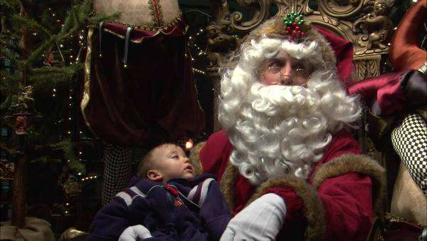Static shot view of a young boy sitting on Santa Claus lap on Christmas day Rights-managed stock video