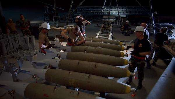 Push-out shot of military mechanics preparing bombs in a warehouse Rights-managed stock video