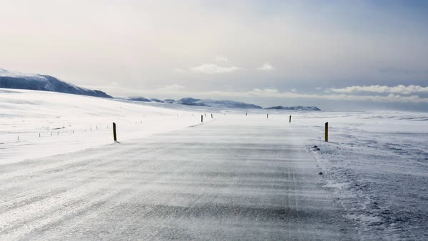 Wide shot of an empty road in winter with blowing snow Royalty-free stock video