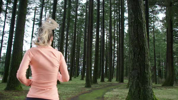 Slow motion of a woman running in a forest Royalty-free stock video