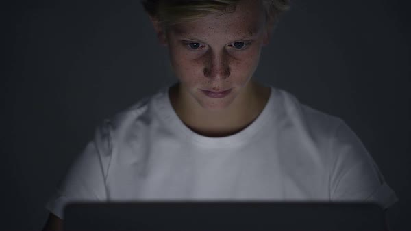Blond teenager student typing on laptop at night face lit by screen only Royalty-free stock video