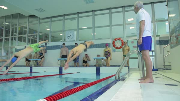 Slow motion shot of swimmers diving from starting block during training in indoor pool with coach Royalty-free stock video