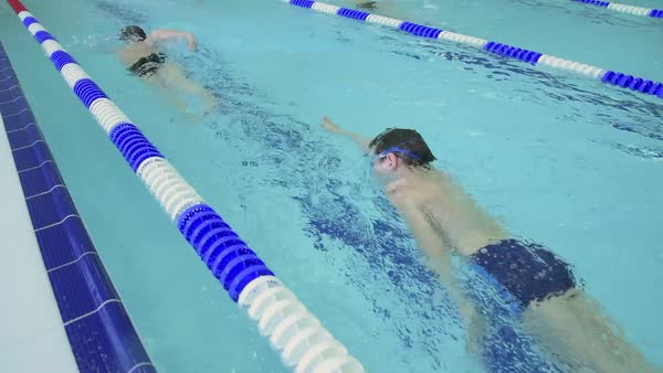 Tracking shot of school children practicing crawl stroke in indoor swimming pool Royalty-free stock video