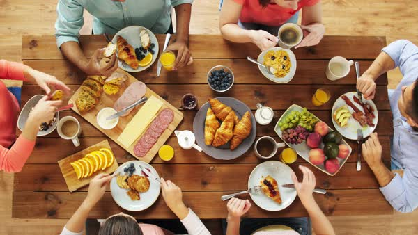 Enjoyable Group Of People Eating At Table With Food Stock Footage Download Free Architecture Designs Embacsunscenecom