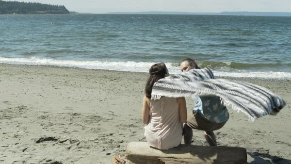 A couple sitting on a beach and covering themselves with a blanket Royalty-free stock video