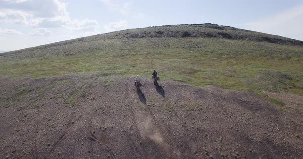 Drone shot of a hilly area with two men riding motorcycles Royalty-free stock video