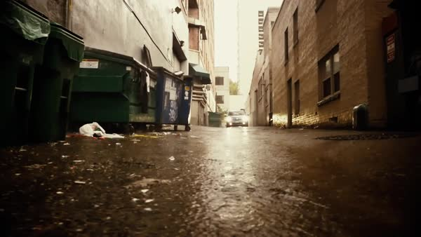 A car slowly drives down an alley in the rain Royalty-free stock video