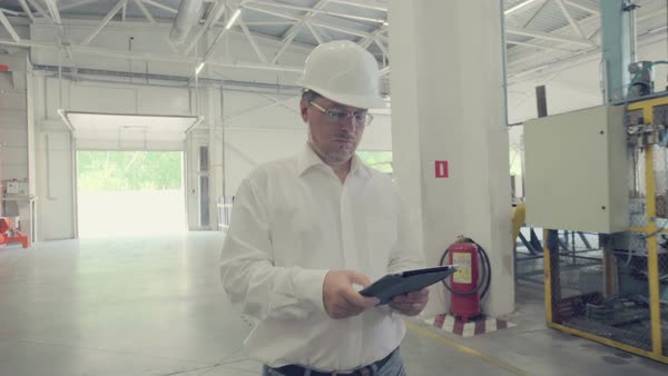 Engineer walking through factory manufacturing plant with tablet Royalty-free stock video