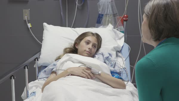 Medium shot of a doctor talking with sick teenage girl