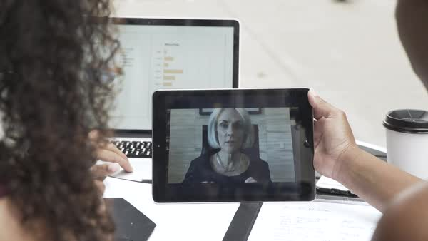 Hand-held shot of three women holding a video conference on a tablet Royalty-free stock video