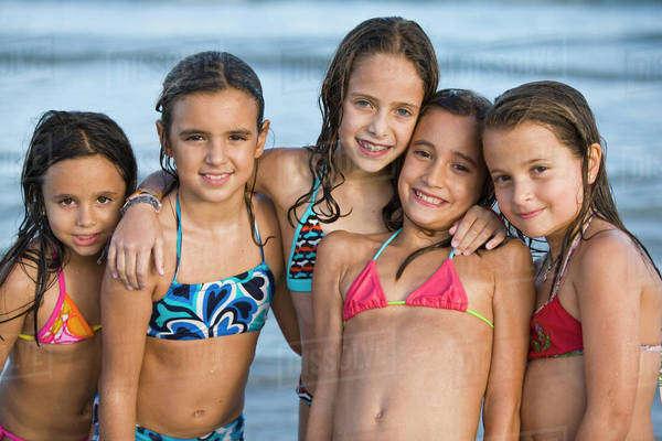 Hispanic Girls In Bikinis Posing On Beach Stock Photo