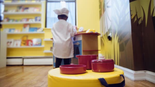 Black girl playing in toy kitchen at daycare Royalty-free stock video