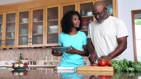 African American couple preparing food in kitchen using recipe on digital tablet Royalty-free stock video