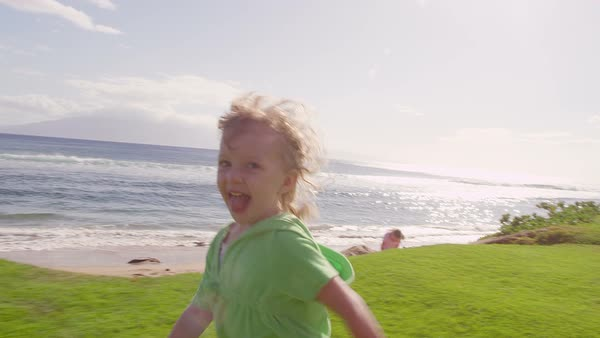 A little girl runs in some grass near the ocean while she smiles for the camera Royalty-free stock video