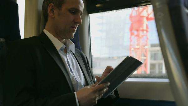 Business Man types into his ipad/digital tablet on a train, medium shot Royalty-free stock video